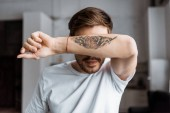 Fotografie handsome young man covering face with arm with tattooed tiger eyes at home