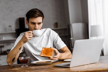 handsome young freelancer eating toast with jam and coffee and looking at laptop screen at home