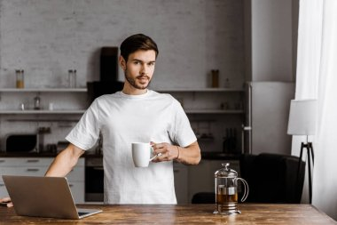 attractive young freelancer with cup of tea and laptop working on kitchen at home