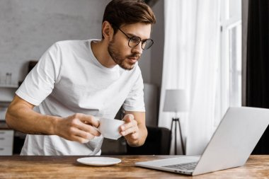 attractive young freelancer with coffee working with laptop at home