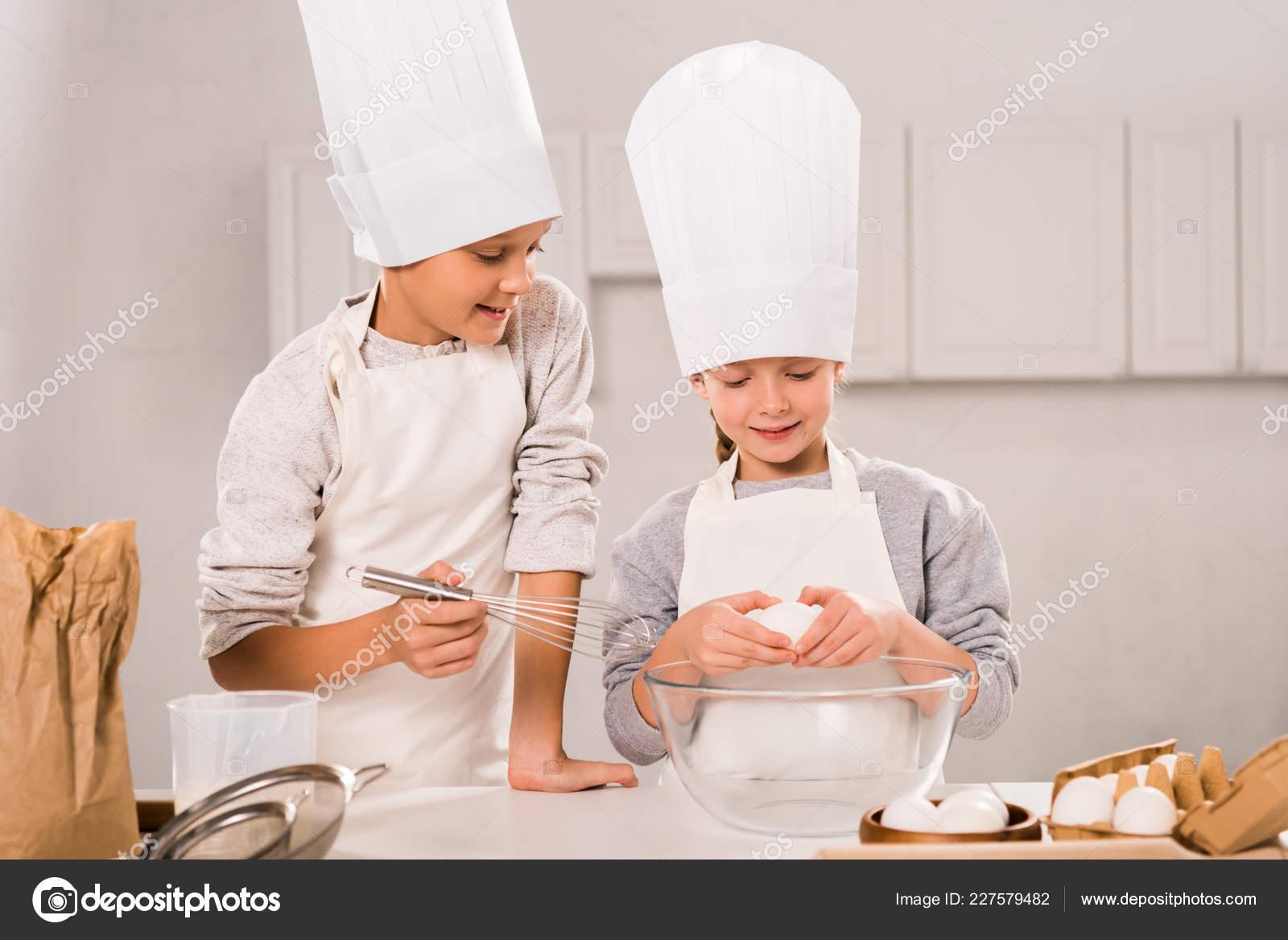 Messa a fuoco selettiva dei bambini in grembiuli e cappelli da chef durante  la preparazione del cibo al tavolo in cucina– immagine stock 0575214f9dd4