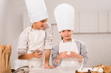 little children in aprons and chef hats preparing at table in kitchen