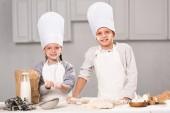 Fotografie Schwester und Bruder in Kochmützen Spaß mit Mehl am Tisch in der Küche