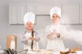 Fotografie málo šťastných dětí v chef klobouky baví s moukou v kuchyni