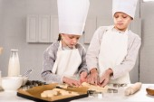 gyerekek a séf sapka és kötények, kivágása a cookie-k a konyha asztalnál tészta