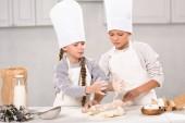 děti v zástěry a čepice šéfkuchař vypečenou s váleček u stolu v kuchyni