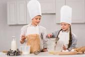 šťastné děti v zástěry prosévání mouky přes síto do mísy u stolu v kuchyni