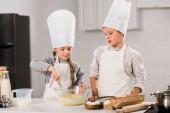 děti v chef klobouky a zástěry šlehání vejce v míse v kuchyni u stolu