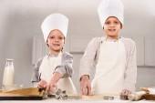 šťastné děti v chef klobouky a zástěry vysekávání těsta pro soubory cookie u stolu v kuchyni