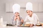 radostné děti v zástěry kartáčování soubory cookie na pekáč v kuchyni