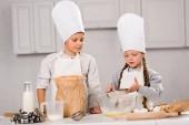 Fotografie Schwester und Bruder in Schürzen Sichten Mehl durch Sieb in Schüssel am Tisch in der Küche