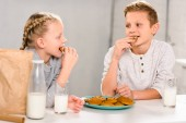 Photo happy children eating cookies and drinking milk at table in kitchen