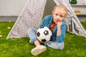 selective focus of kid with soccer ball looking at camera while sitting on green lawn near tent at home