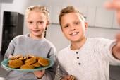 Selektivní fokus Boy s selfie s sestrou zatímco ona drží desku s cookies