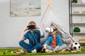 Fotografie Bruder und Schwester mit virtual-Reality-Headsets in der Nähe von Wigwam zu Hause