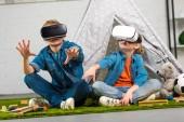 Fotografie Kinder mit virtual-Reality-Headsets und Gestikulieren mit den Händen in der Nähe von Wigwam zu Hause
