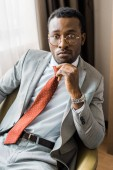 Fotografia uomo daffari americano africano Pensive in abito grigio e cravatta rossa che si siede in poltrona