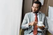 vážnou americký podnikatel držící šálek kávy a při pohledu na okna