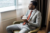 Fotografie african american businessman holding coffee cup and looking at window