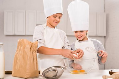 smiling sister and brother breaking eggs into bowl during food preparation at table in kitchen