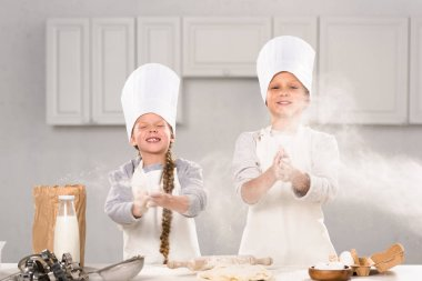 little happy children in chef hats having fun with flour in kitchen