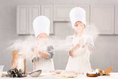 selective focus of brother and sister in chef hats having fun with flour in kitchen