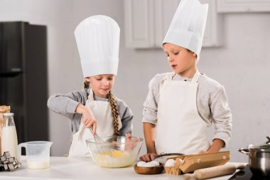 children in chef hats and aprons whisking eggs in bowl at table in kitchen