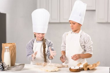 little kids in aprons and chef hats making dough with rolling pin at table in kitchen