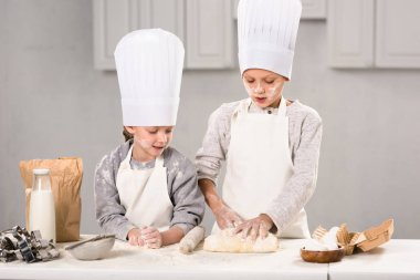 Children in aprons and chef hats making dough with rolling pin at table in kitchen stock vector