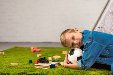 adorable boy laying with soccer ball on green lawn at home