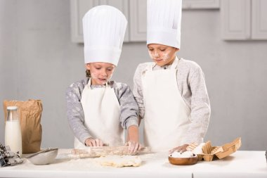 sister and brother in aprons and chef hats making dough with rolling pin at table in kitchen