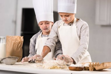 selective focus of kids in aprons and chef hats making dough with rolling pin at table in kitchen