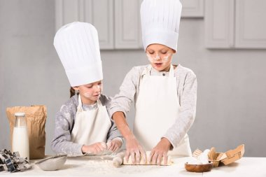 focused kids in aprons and chef hats making dough with rolling pin at table in kitchen