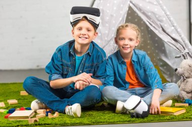 smiling children with virtual reality headsets sitting near wigwam at home