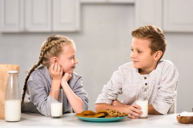 smiling kids looking at each other and sitting at table with cookies and milk in kitchen