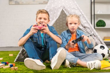 adorable sister and brother playing with joysticks near wigwam at home