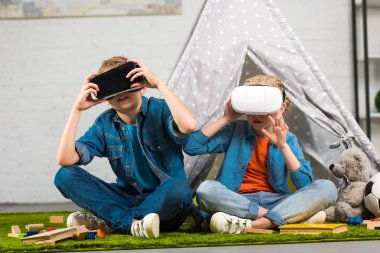little children using virtual reality headsets near wigwam at home