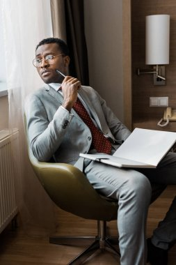 handsome pensive african american businessman with journal sitting in hotel room