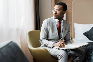 handsome african american businessman with journal in hotel room