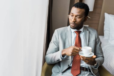 serious african american businessman holding cup of coffee and looking at window
