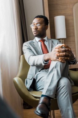 thoughtful african american businessman in gray suit sitting in armchair in hotel room