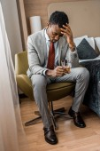 Photo frustrated african american man holding glass of cognac in hotel room