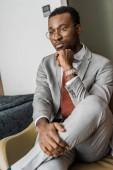 nachdenklich afrikanische amerikanische Geschäftsmann in graue Jacke sitzen in Hotelzimmer