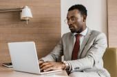 zaměřuje americký podnikatel psaní na přenosný počítač v hotelovém pokoji