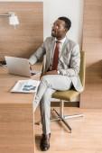 americký podnikatel pracuje na přenosný počítač v hotelovém pokoji s novinami
