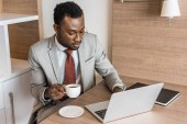 african american businessman in suit holding cup of coffee while working on laptop in hotel room