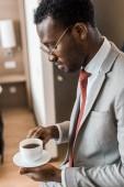 Fotografie african american businessman looking at cup of coffee in hotel room