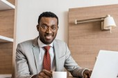 smiling african american businessman with laptop on coffee break in hotel room