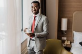 Fotografie cheerful african american businessman holding coffee cup in hotel room