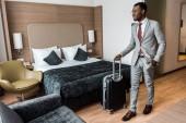 usmívající se americký podnikatel s cestovní taškou v hotelovém pokoji